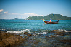 Fishing boat near coast. Picture of small fishing boat floating near coast line on a bright sunny day. Ko Bon, Thailand Stock Photo
