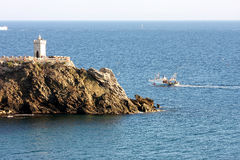 Fishing boat near the lighthouse of Piombino, Italy Royalty Free Stock Photo