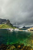 Fishing boat near scenic village Reine on Lofoten islands near green water and mountains Royalty Free Stock Photography