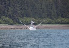 Fishing boat near shore with stabilizers extended. Fishing boat near the shore in Southeast Alaska with forest in the background Stock Photos
