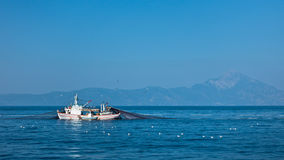 Fishing boat with nests at sea in front of mountain Athos Royalty Free Stock Photos