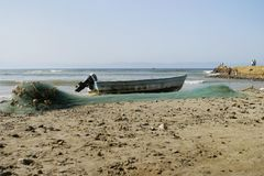 Fishing Boat and Net. A small fishing boat or skiff that has been pulled up on the beach after the day's fishing is over. The fish net is organized in front of stock images