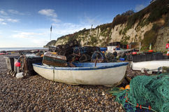 Fishing boat and nets on the beach in Devon. A fishing boat with nets and lobster pots on the beach at Beer on the Jurassic Coast in Devon Stock Photo