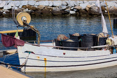 Fishing boat with nets on board docked to the cliff in Versilia Royalty Free Stock Image