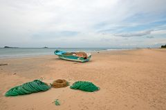 Fishing boat next to ropes and nets on Nilaveli Beach in Trincomalee state in Sri Lanka stock images