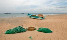 Fishing boat next to ropes and nets on Nilaveli Beach in Trincomalee state in Sri Lanka royalty free stock photos