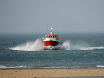 Fishing boat in Norfolk heads for shore stock photography