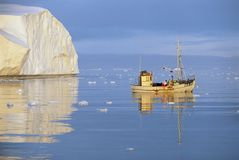 Fishing Boat on Ocean by Iceberg Royalty Free Stock Photos