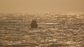 Fishing boat in ocean. Fishing boat rocking on the waves in the rays of the setting sun, Mui Ne, Vietnam stock footage