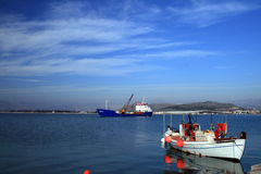 Fishing boat and old cargo ship - Greece Royalty Free Stock Images