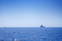 Fishing-boat on open sea. Sailboat and fishing boat on open sea on a sunny summer day royalty free stock photos