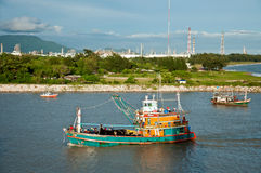 Fishing boat over petrochemical zone Royalty Free Stock Image