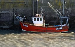 Fishing boat, Padstow, Cornwall, UK. A small red hulled fishing boat alongside at Padstow Harbour, Cornwall, UK Royalty Free Stock Photo