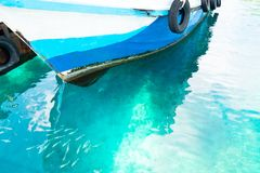 Fishing boat parked at the pier in the beautiful blue sea and fish in the sea royalty free stock photo