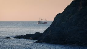 Fishing Boat Passes Behind Rocks At Sunset. Fishing boat sailing past coastal rocks in pretty evening lighting stock video