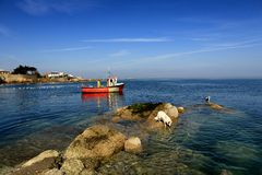 Fishing boat passes rocks royalty free stock image