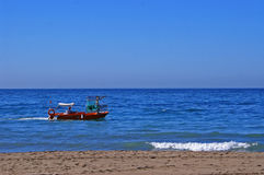 Fishing boat passing by Malagueta beach in Malaga. A fishing boat passing by the beach around noon in Malaga, Spain Royalty Free Stock Photos