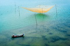 Fishing boat with people in national dress and fishing net in Vietnam stock photo