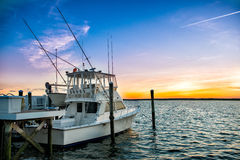 Fishing boat on the pier at sunset on the lake Royalty Free Stock Image