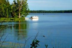Fishing boat on calm lake near Bemidji Minnesota. Fishing boat and pontoon on calm Lake Movil near Bemidji Minnesota on a beautiful evening stock photos
