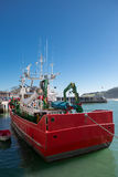 Fishing boat in port of Lekeitio. Big red fishing boat in the port of Lekeitio with blue sky, Bizkaia, Basque Country, Spain Royalty Free Stock Image