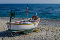 Fishing boat pulled ashore on the beach. Of Noli in Liguria with the blue sea in the background royalty free stock photography