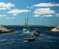 Fishing Boat Pulling Barges. Fishing boats moving out of the harbor in Peggy's Cove, Nova Scotia, Canada Royalty Free Stock Photos