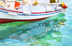 Fishing boat reflected on sea Aegina island Greece Royalty Free Stock Photos