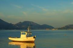 Fishing boat reflecting on sea Stock Photo