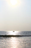 Fishing boat in the reflection of the sun on the water, Sri Lanka Royalty Free Stock Photo