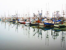 Fishing Boat Reflections. Colorful fishing vessels at the wharf with beautiful reflections in the ocean water Stock Photo