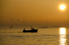 Fishing Boat Returns. A fishing boat returns to port under a glowing sunset in the Isles of Scilly, Cornwall Stock Photos