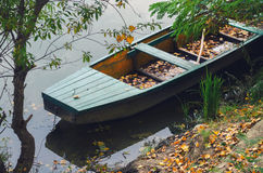 Fishing boat at river shore covered fallen autumn leaves Royalty Free Stock Photography