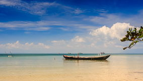 Fishing Boat Rocks by Beach in Shallow Bay in Vietnam. Vietnamese fishing boat rocks in shallow bay by beach against blue sky and boats on horizon stock footage