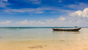 Fishing Boat Rocks by Beach in Shallow Bay in Vietnam. Vietnamese fishing boat rocks in shallow bay by beach against blue sky and boats on horizon stock video footage