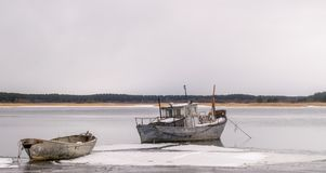 A fishing boat and a rowing boat in a frozen lake or sea. royalty free stock photos