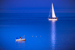 Fishing boat and sailing boat meet in the blue sea. Stock Images