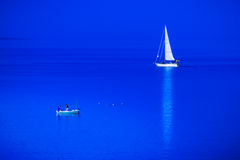 Fishing boat and sailing boat meet in the blue sea. Stock Image