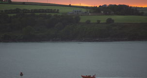 Fishing boat sailing early in the morning with the sunrise in the background Stock Images