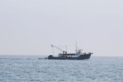 Fishing boat sailing at sea stock photos