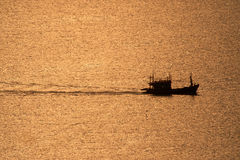 Fishing boat sailing in the sea during sunset . Royalty Free Stock Photo