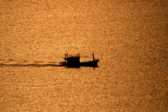 Fishing boat sailing in the sea during sunset . Stock Images