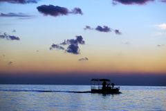 Fishing boat sailing at sunset royalty free stock images