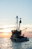 Fishing boat sailing at sunset Royalty Free Stock Photo