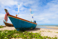 Fishing boat on sand beach and blue sky Stock Photos