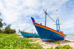 Fishing boat on sand beach and blue sky Royalty Free Stock Image
