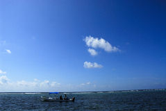 Fishing boat in sea. Small fishing boat in sea with blue sky and cloudscape background Royalty Free Stock Photography