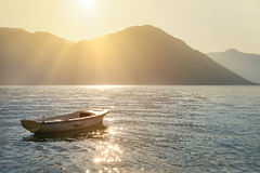 Fishing boat at sea against sunset mountains with sun rays Stock Photo