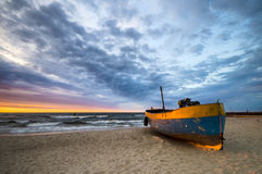 Fishing boat on the sea beach during sunset Stock Photos