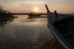 Fishing boat on a sea coast at the sunrise in morning Stock Image